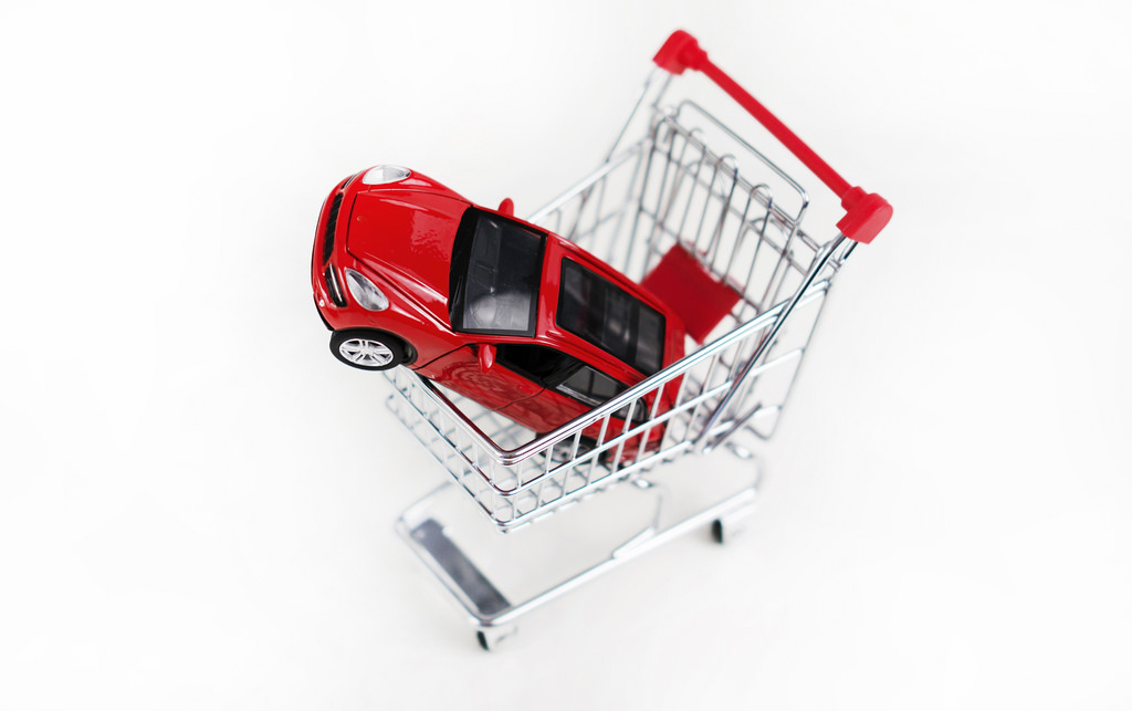 an image of a toy car in a shopping trolley, indicating the car buying process